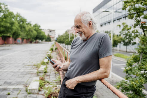Smiling senior man using smart phone while standing by railing in city - MEUF01190