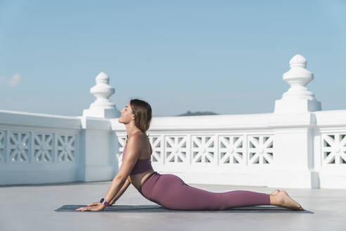Young woman practicing cobra pose on building terrace against clear sky - MTBF00514