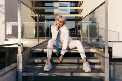 Young woman wearing white suit sitting on steps against modern building - TCEF00885