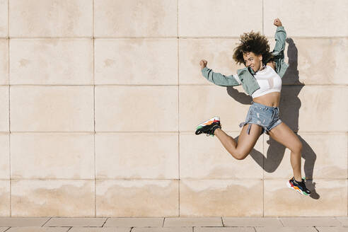 Excited young woman jumping against wall during sunny day - XLGF00307