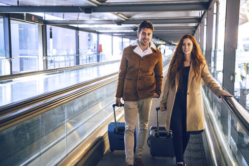 Business couple with luggage walking on moving walkway at airport - EHF00459
