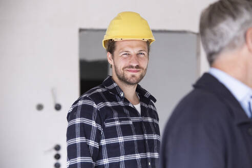 Smiling construction worker standing with architect in constructing home - MJFKF00432