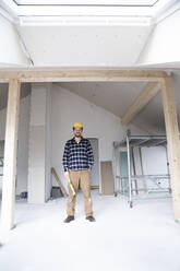 Construction worker standing in house under construction - MJFKF00438