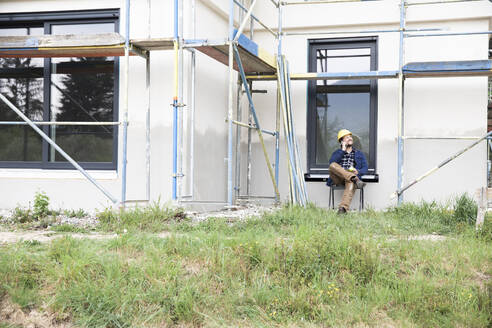 Construction worker talking over mobile phone while sitting against house - MJFKF00450