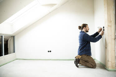 Construction worker installing wires in renovating house - MJFKF00474