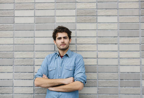 Handsome casual businessman with arms crossed standing against brick wall - SODF00825