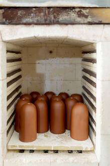 Close-up of brown ceramics in kiln at workshop - EGAF00407