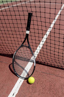 Tennis racket with ball by net in court during sunny day - EGAF00408