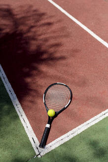 Tennis ball with racket on floor in sports court - EGAF00420