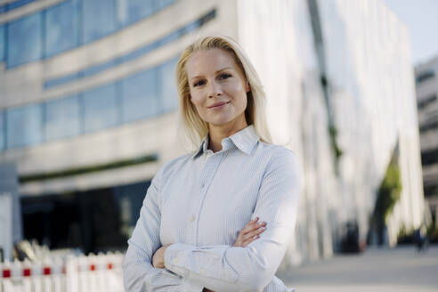 Beautiful blond female entrepreneur smiling while standing with arms crossed at financial district - JOSEF01034