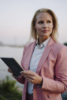 Thoughtful blond businesswoman looking away while holding digital tablet against sky - JOSEF01091