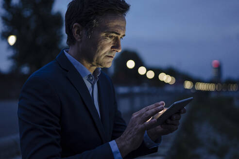 Mature businessman using tablet on a promenade at dusk - JOSEF01171