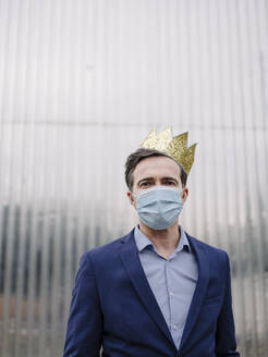 Portrait of a mature businessman wearing a toy crown and protective face mask - JOSEF01210