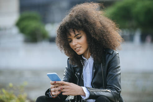 Young afro woman surfing internet on smart phone - KIJF03173