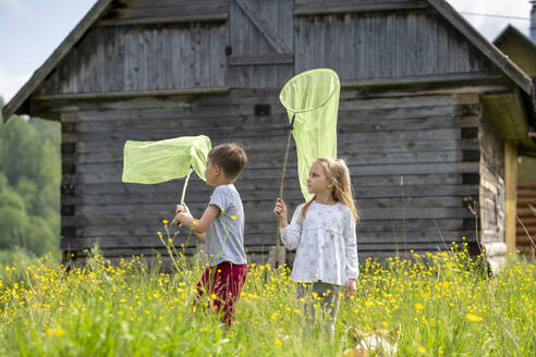 Friends catching butterflies with nets while standing amidst plants against cottage - VPIF02539