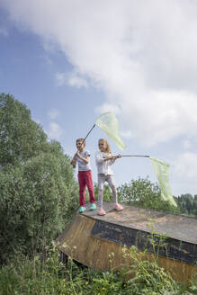Friends catching butterflies with nets while standing on abandoned boat against sky - VPIF02542
