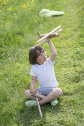 Playful boy flying model airplane while sitting on grassy land - VPIF02551