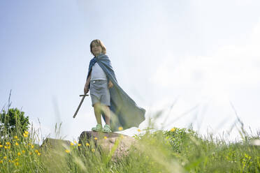 Playful boy wearing cape standing on rock against sky during sunny day - VPIF02554
