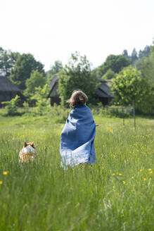 Boy wearing cape standing with dog on grassy land against clear sky - VPIF02557
