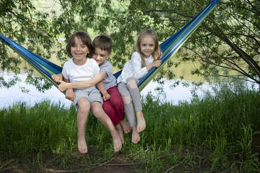 Cheerful friends sitting on hammock in forest - VPIF02560