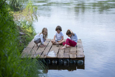 Happy children playing on pier over lake in forest - VPIF02569
