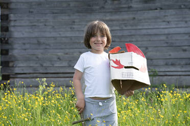 Smiling boy holding mask and toy while standing amidst plants against cottage - VPIF02572
