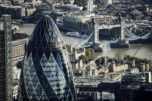 Aerial view of The Gherkin office building and Tower Bridge over the river Thames in London. - CUF55520