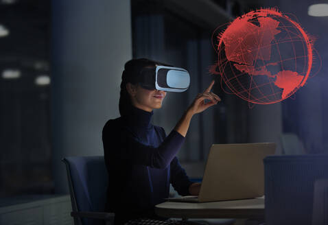Businesswoman with virtual reality glasses touching virtual globe - CAIF28206