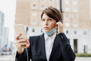 Businesswoman holding smart phone listening music through headphones while standing in city - MEUF01209