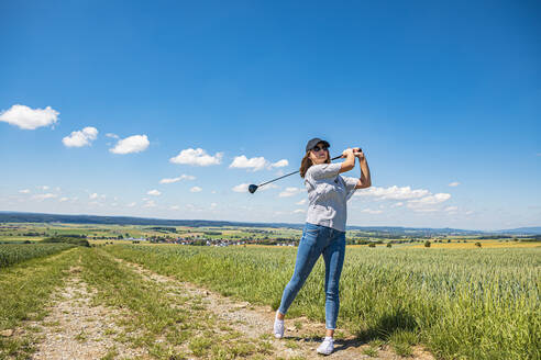 Young woman playing golf at countryside - VTF00625