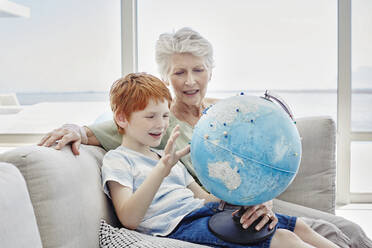 Grandmother and grandson sitting on couch in a villa looking at globe - RORF02249
