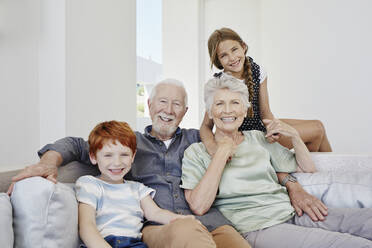 Portrait of happy grandparents with grandchildren on a couch in a villa - RORF02273