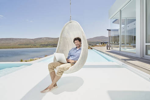 Man sitting in hanging chair above swimming pool using laptop - RORF02276
