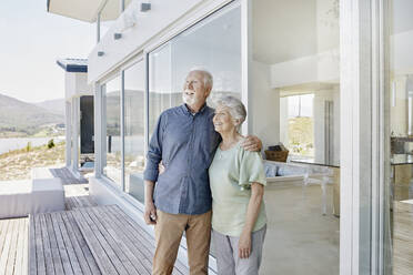 Happy senior couple standing at luxury beach house - RORF02300