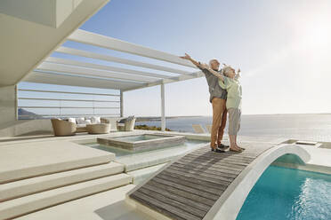 Carefree senior couple standing on bridge above a swimming pool at a luxury beach house - RORF02309