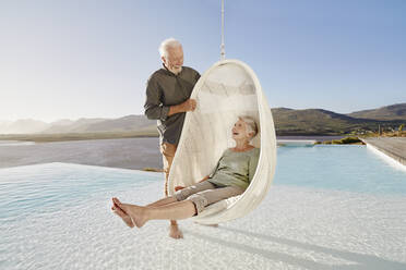 Happy senior couple with woman sitting in hanging chair above swimming pool - RORF02321