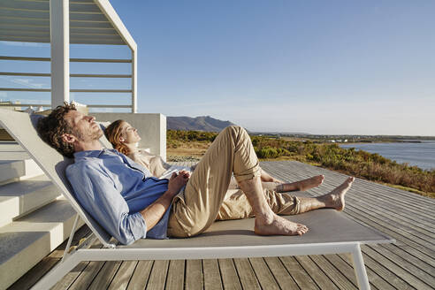 Couple lying on deck chairs at luxury beach house - RORF02324
