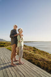 Senior couple enjoxing the view on wooden terrace at the sea - RORF02327