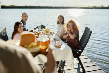 Friends having dinner at a lake with man serving cheese platter - ZEDF03570
