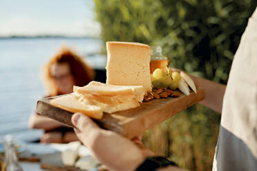 Man serving cheese platter for friends at a lake - ZEDF03573