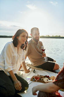 Friends having picnic on jetty at a lake at sunset - ZEDF03585