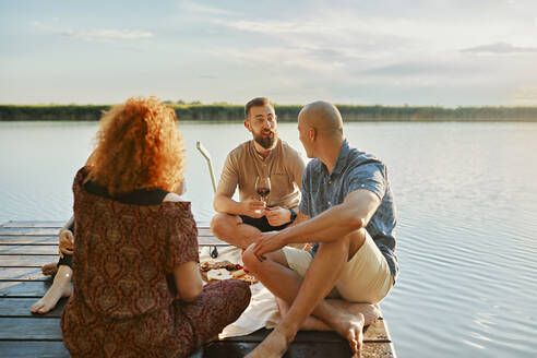 Friends having picnic on jetty at a lake - ZEDF03588
