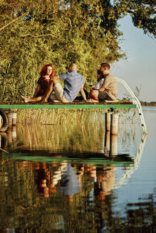 Friends having picnic on jetty at a lake - ZEDF03591