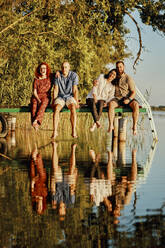 Happy friends reflected in water sitting on jetty at a lake - ZEDF03594