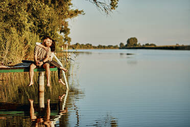 Affectionate couple reflected in water sitting on jetty at a lake - ZEDF03600