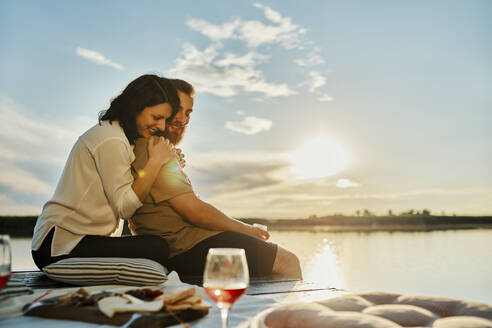 Couple having picnic on jetty at a lake at sunset - ZEDF03603