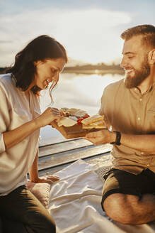 Couple having picnic on jetty at a lake at sunset eating cheese - ZEDF03615
