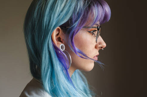 Close-up of thoughtful young woman with dyed hair and piercings against wall in old office - JMPF00126