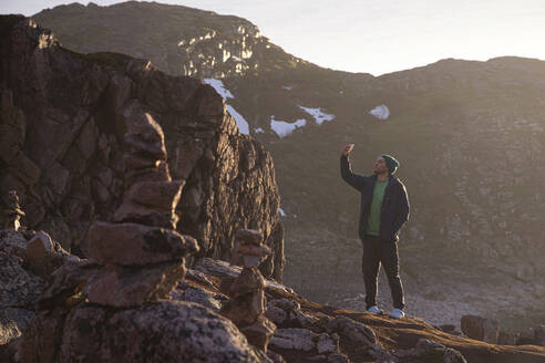 Man taking selfie while standing on rocky mountain at Teriberka, Murmansk Oblast, Russia - KNTF04907