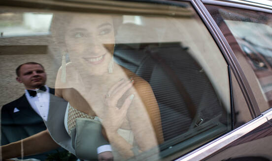 Beautiful young female in wedding dress smiling and looking at groom while sitting inside car - ADSF00124